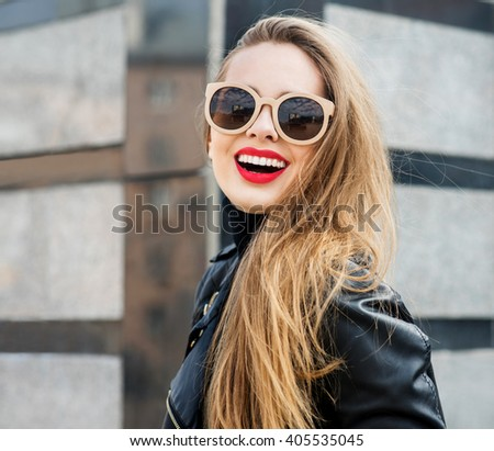 Fashion portrait stylish pretty woman in sunglasses outdoor. Young smiling woman wearing a rock black style having fun in city. Street fashion. Red lipstick. - stock photo