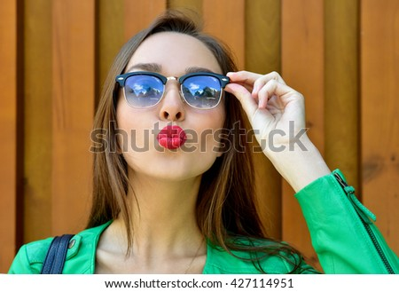 Fashion portrait stylish pretty woman in sunglasses posing in the city in a green jacket . Street fashion Beautiful Young Woman Outdoors. Blowing lips kiss. - stock photo