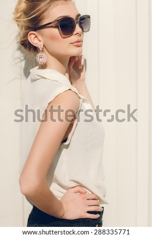 Fashion portrait stylish pretty woman in sunglasses posing in the city, street fashion - stock photo
