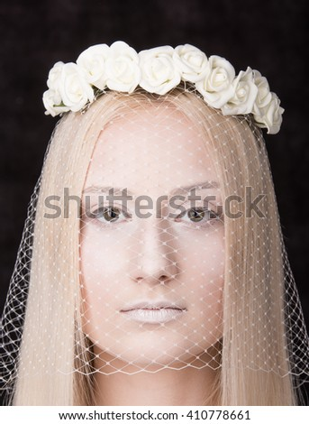Fashion portrait. The young woman's face close up with veil and wreath of white roses in her hair against a dark background. Neutral facial expression - stock photo
