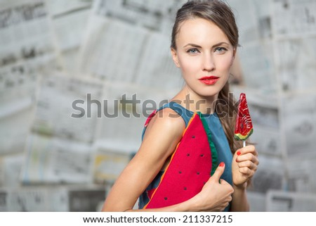 Fashion portrait with a sexy girl with watermelon lollipop against grunge old paper grey background. copy space - stock photo