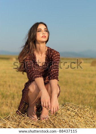 fashion portrait woman sitting on a hay stack with wind in her hair - stock photo