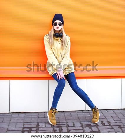 Fashion pretty blonde girl in city over colorful orange background - stock photo