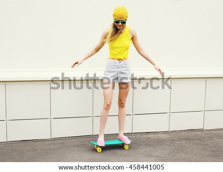Fashion pretty girl riding on skateboard in city over white background