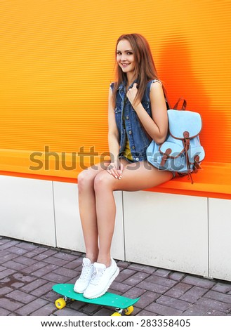 Fashion pretty girl with skateboard and backpack against the colorful orange wall - stock photo