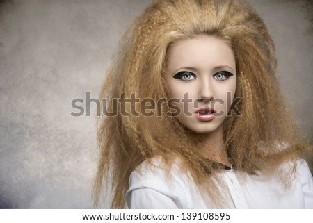 fashion pretty rock girl with dark glossy make-up, creative hair-style in close-up portrait on grunge background