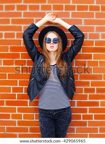 Fashion pretty woman model in black rock style over bricks background - stock photo