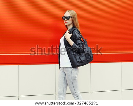 Fashion pretty woman wearing a rock black leather jacket, sunglasses and bag in profile over red background - stock photo