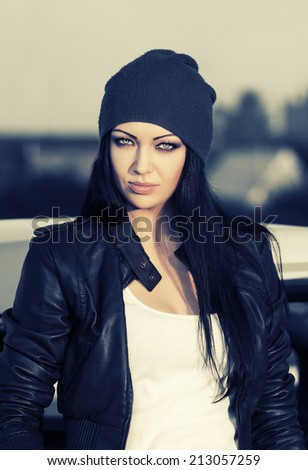 Fashion punk woman in leather jacket standing at the car - stock photo