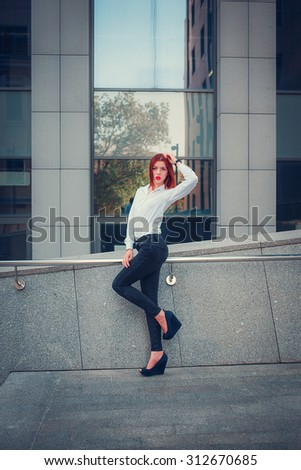 Fashion redhead young woman walking outdoor on street