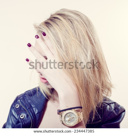 fashion rock star series: portrait of hiding in her own blonde hair sexy pretty girl in leather jacket posing over light copy space background - stock photo