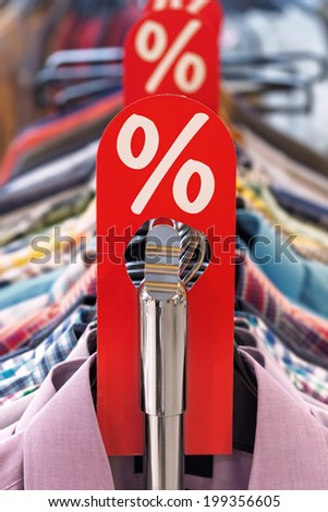 Fashion sale rack with a red label, shirts and hangers in a row. Shallow depth of field. - stock photo