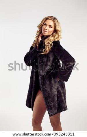 Fashion seductive blond hair lady in an elegant fur coat and black underwear - stock photo