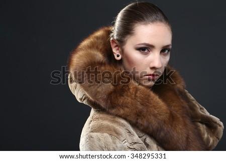 Fashion seductive brown hair lady in an elegant fur coat a on a dark background - stock photo