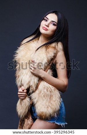 Fashion seductive dark hair lady in an elegant fur coat, dark underwear a on a dark background