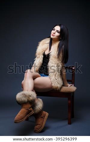 Fashion seductive dark hair lady in an elegant fur coat, dark underwear a on a dark background - stock photo