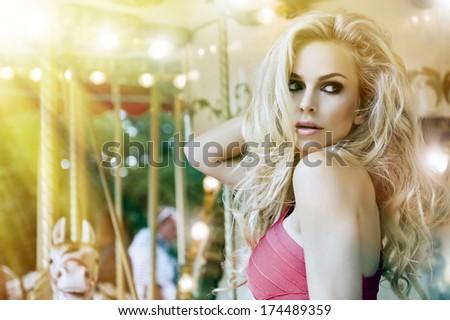 Fashion sexy model posing on carousel - stock photo