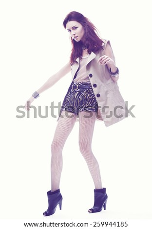 fashion sexy model woman in a jacket and shorts poising on a white background