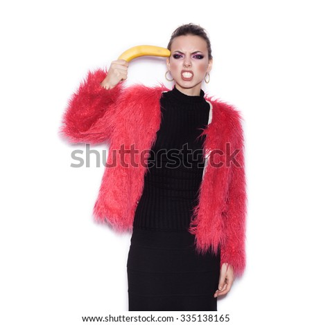 Fashion sexy woman wearing black dress and pink fur coat making fun with banana. Cute girl having fun over white background not isolated - stock photo
