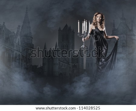 Fashion shoot of beautiful woman in a long dress over ancient background - stock photo