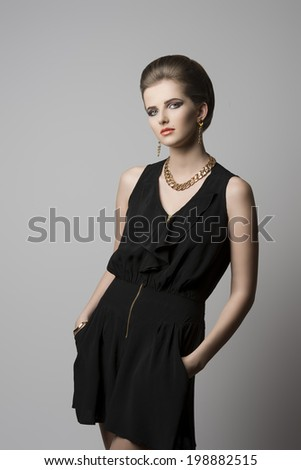 fashion shoot of young elegant girl with cute hair-style and make-up, black dress and golden jewellery   - stock photo