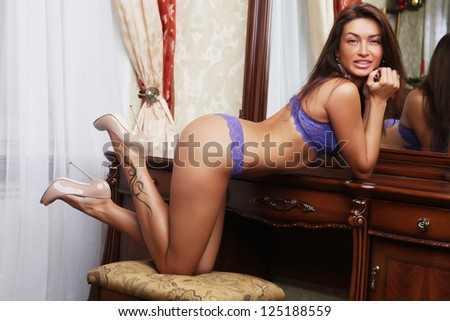Fashion shoot of young sexy striptease dancer in hotel room - stock photo