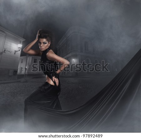 Fashion shoot of young sexy woman in black long dress - stock photo