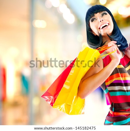 Fashion Shopping Girl Portrait. Beauty Woman with Shopping Bags in Shopping Mall. Shopper. Sales. Shopping Center - stock photo