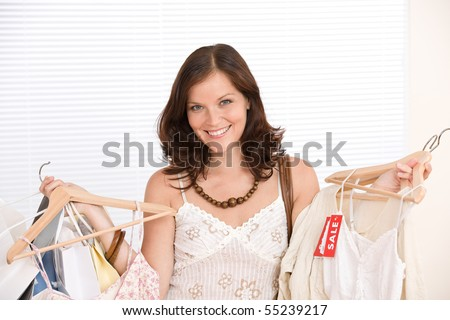 Fashion shopping - Happy woman choose sale clothes, holding shopping bag