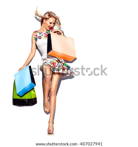 Fashion Shopping Sexy Model Girl full length Portrait. Beauty Woman with Shopping Bags in short white dress isolated on White. Blowing blond hair, high hills. Shopper. Sales  - stock photo