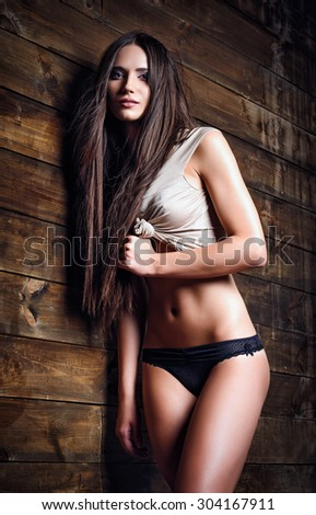 Fashion shot: a beautiful girl in panties and shirt stands at the wood wall - stock photo