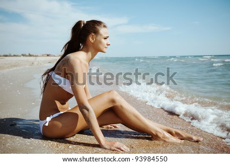 Fashion shot of a beautiful girl in a white swimsuit sitting on the beach. Kazantip, Crimea