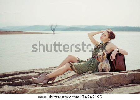Fashion shot of a beautiful girl  lying on the shore of the lake with a suitcase and a dog (Yorkshire terrier) - stock photo