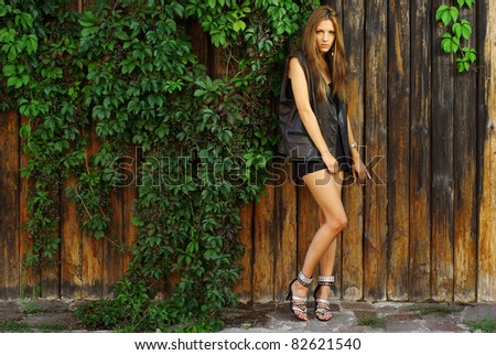 Fashion shot of a beautiful model posing at the vineyard wall - stock photo