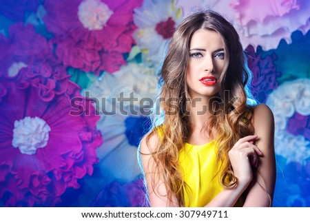 Fashion shot of a beautiful model posing on a background of bright large flowers. Beauty, fashion. Summer inspiration. - stock photo