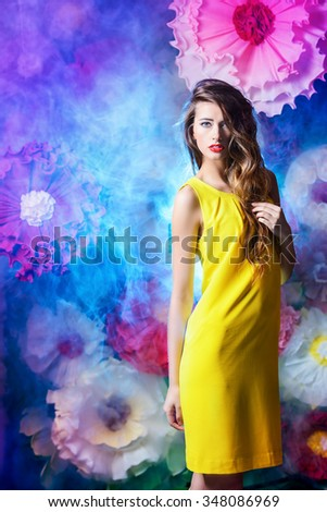Fashion shot of a beautiful model posing on a background of bright large flowers. Beauty, fashion. Summer inspiration.