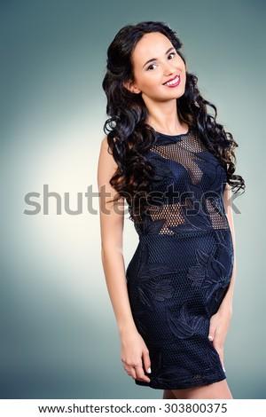 Fashion shot of a beautiful pregnant woman wearing elegant evening dress. Studio shot. - stock photo