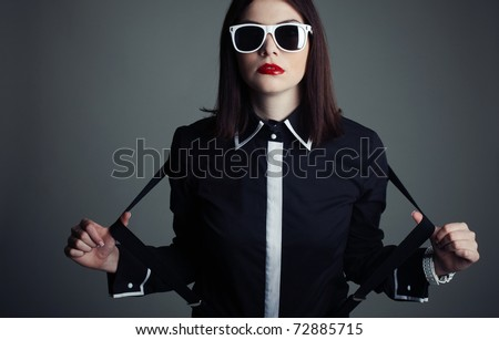 Fashion shot of a beautiful, professional model in black shirt, sunglasses and suspenders - stock photo