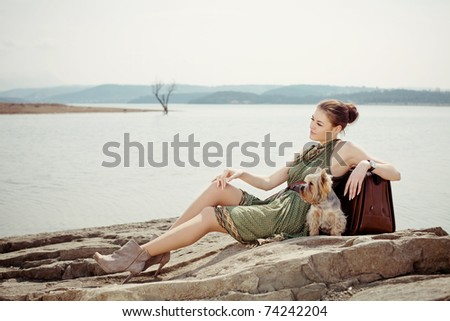 Fashion shot of a beautiful, professional model on the lake with a suitcase and a dog (Yorkshire terrier)