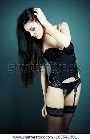 Fashion shot of a beautiful sexy girl in a black underwear. Posing in studio - stock photo