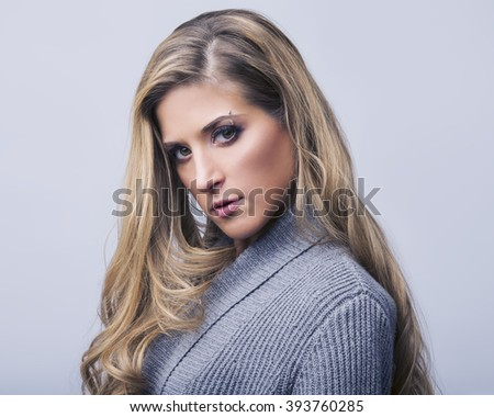Fashion shot of a beautiful woman in a grey sweater on a white background