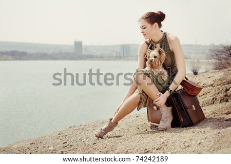 Fashion shot of a beautiful woman sitting on suitcase on the banks of the lake with the dog (Yorkshire terrier) - stock photo