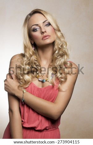 fashion shot of a blond girl , in color summer dress , with fresh necklace , looking in camera