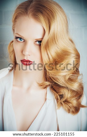 Fashion shot of a glamorous blonde woman with retro make-up and hairdo. - stock photo