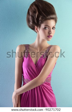 fashion shot of a gorgeous brunette with a a fashion hair up-do and wearing an elegant pink evening dress with small pearls - stock photo