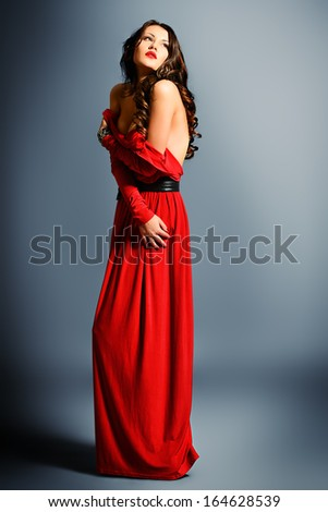 Fashion shot of a gorgeous young woman in elegant red dress.