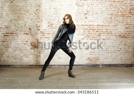Fashion shot of a gorgeous young woman wearing leather jacket, pant and shoes.