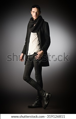 Fashion shot of a handsome male model in black suit posing in motion over gray background. Men's beauty. - stock photo