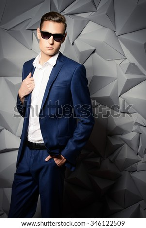 Fashion shot of a handsome young man in elegant classic suit and sunglasses. - stock photo