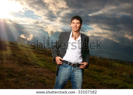 Fashion shot of a handsome young man that stays at the field, he is smiling. Outdoor.